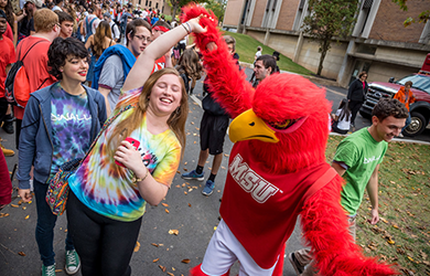 Student dancing with red hawk mascot